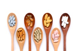 Various types of medicine pill capsules and tablets in wooden spoon isolated on white background. Healthy supplement , herbal, vitamin and dietary concept. Top view. Flat lay.