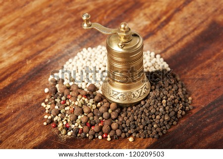 various types of pepper on wood with metal hand mill