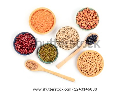 Photo of  Various types of pulses, shot from the top on a white background. Red kidney, pinto, and black beans, lentils, chickpeas, soybeans, and black-eyed peas