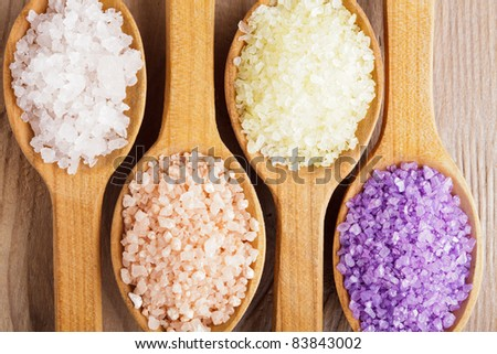 Various types of spa sea salt in wooden spoons closeup