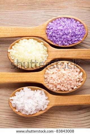 Various types of spa sea salt in wooden spoons closeup