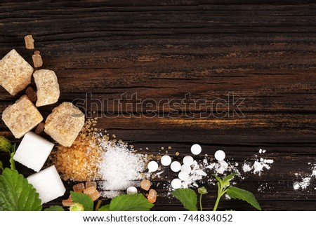 Various types of sugar - brown, white, crystal, cane and powdered sugar and artificial sweetener from above.