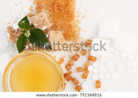 Various types of sugar -  brown, white, crystal, powdered and cane sugar, artificial sweetener and honey in bowl from above.