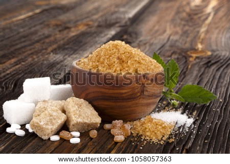 Various types of sugar, brown, white, crystal sugar, artificial sweetener, cane sugar and aztec sweet herb on wooden table.