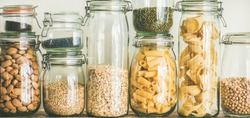 Various uncooked cereals, grains, beans and pasta for healthy cooking in glass jars on wooden table, white background, close-up. Clean eating, vegan, balanced dieting food concept