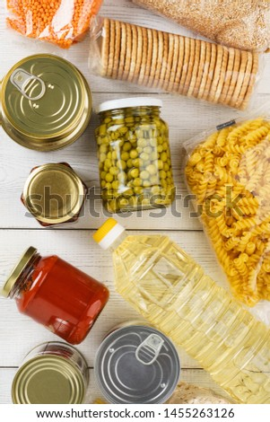 Various uncooked cereals, grains, pasta and canned food on a white wooden table. Flat lay.