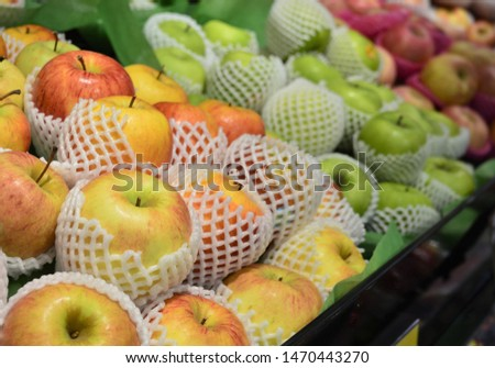 Various varieties of apples wrapped with foam mesh that are sold in the chemical-free fruit market. Close up