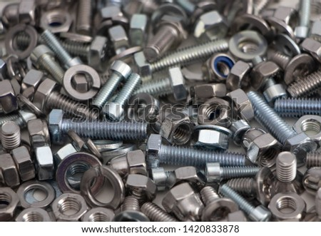 various, various bolts, nuts, screws and washers lying all together in a heap, top view