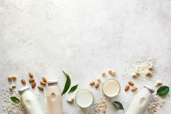 Various vegan plant based milk and ingredients, top view, copy space. Dairy free, lactose free nut and grains milk, substitute drink, healthy eating.
