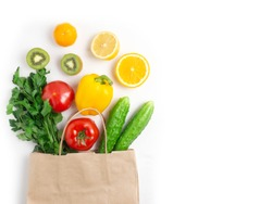 Various vegetables and fruits in the bag on a white background, top view, laid out in a circle. The concept of healthy eating, food background.