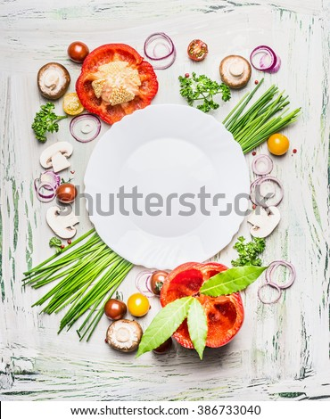 Various vegetables and seasoning cooking  ingredients around blank plate on light  rustic wooden background, top view composing. Healthy eating and diet food concept.