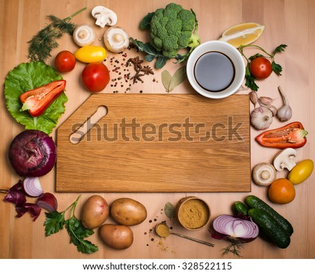 Various vegetables and spices and empty cutting board. Colorful ingredients for cooking on rustic wooden table around empty cutting board with copyspace. Top view. Retro styled.