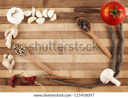 various vegetables and spices forming a frame on cutting board