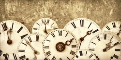 Various vintage clock faces in front of an old concrete wall