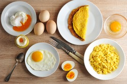 Various ways of cooking chicken eggs. Omelette, poached, soft-boiled, hard-boiled, fried, scrambled eggs.  Top view. Close-up.