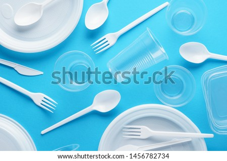 Various white plastic disposable tableware on blue background. Creative flat lay. Foto stock ©