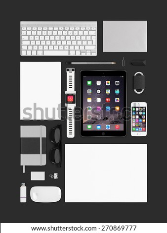 Varna, Bulgaria - February 10, 2015: Top view of branding identity technology Apple products mockup. Consists of ipad air 2, smart watch, iphone 5s, keyboard, notebook, magic mouse, flash drive, paper