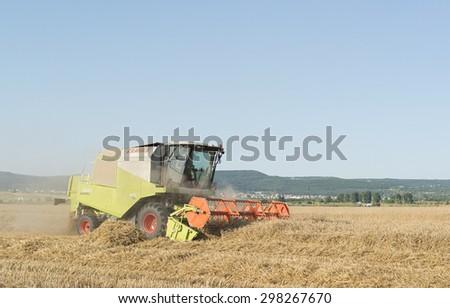 VARNA, BULGARIA - JULY 19, 2015: Claas Avero 240 combine harvester harvesting wheat in field close to the city of Varna. #298267670