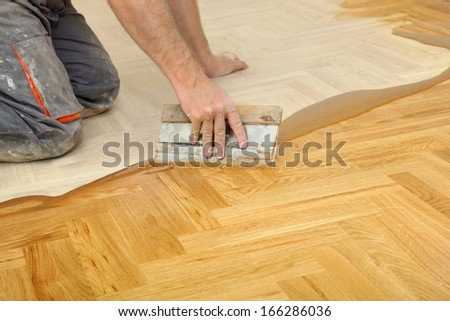 Varnishing of oak parquet floor, workers hand and tool
