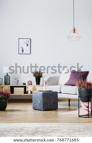 Vase and candle on grey pouf next to wooden cupboard and couch with purple pillow in living room interior with heathers