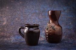 Vase d'argile avec glaçure avec des fleurs, et un laitier d'argile, sur un fond sombre hétéroclite