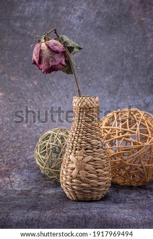 vase en osier avec une fleur et une rose sèche à l'intérieur, avec des boules en osier de rotin, sur un fond hétéroclit Photo stock ©