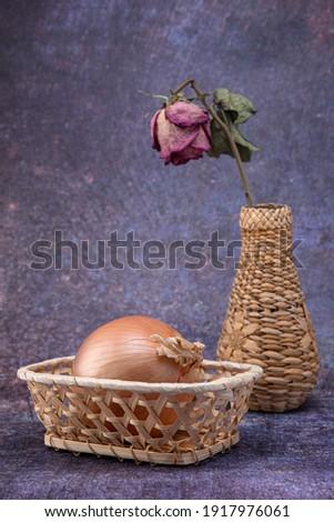 Vase en osier avec une fleur et une rose sèche à l'intérieur, et un panier avec des oignons, sur un fond hétéroclite Photo stock ©