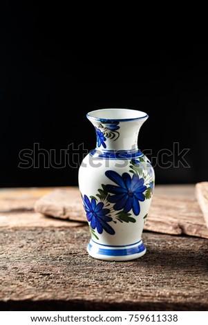 Stock Photo Vase  flowers on wooden floor, black background.