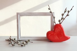 Vase in the shape of a heart with flowering willow branches, photo frame on the background of a white wall with shadows from the window, side view