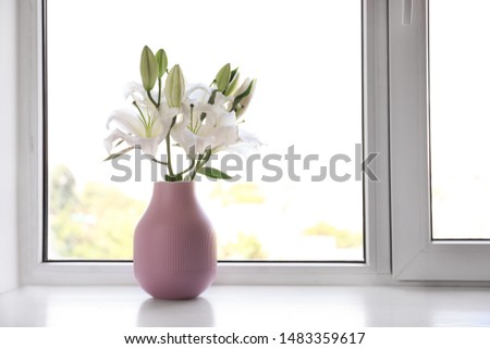 Vase of beautiful lilies on windowsill indoors, space for text