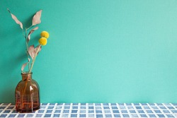 Vase of dry flowers on blue ceramic mosaic tile table. mint wall background. Home interior