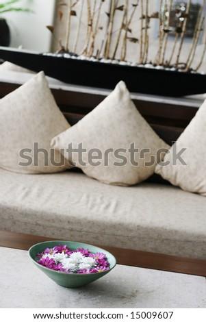 Vase of flowers floating in water in a living room.