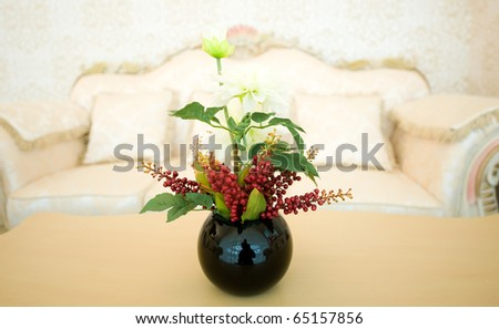 vase of flowers in a hotel room on coffee table.