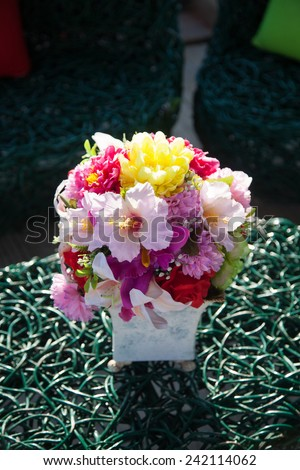 Vase of flowers on the table. Variety of colorful flowers arranged in a vase shape.