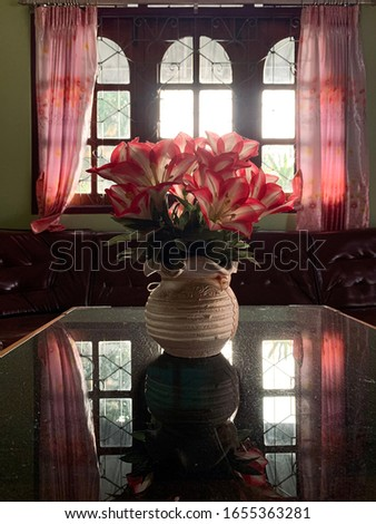Vase of flowers under table background with brown sofa and window