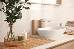 Vase with beautiful branches, candles and fresh towels near vessel sink in bathroom. Interior design