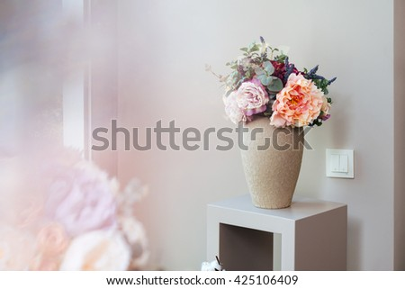 Vase with beautiful fresh flowers standing on small table