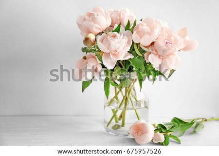 Vase with beautiful peony flowers on table