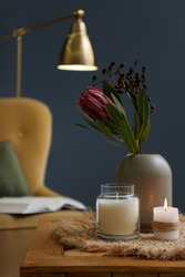 Vase with beautiful protea flowers and candles on wooden table indoors. Interior elements