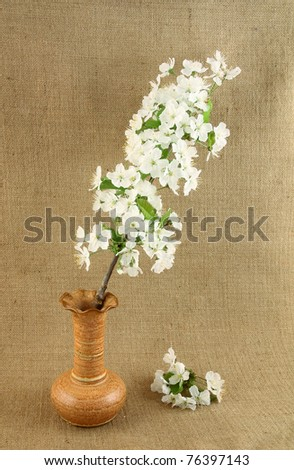 Vase with cherry twigs on jute background