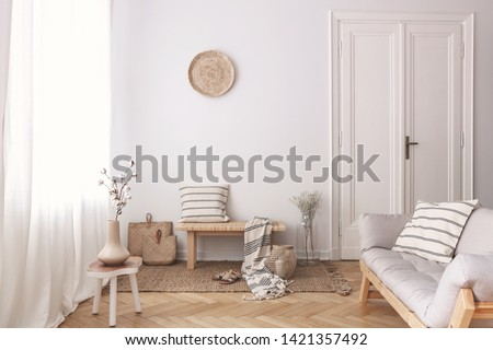 Vase with cotton flower on wooden table next to couch in stylish beige apartment
