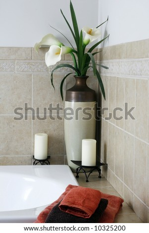vase with flowers and candle decor in bathroom