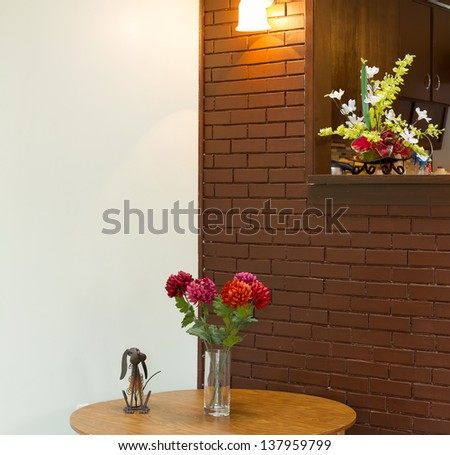 Vase with  flowers on the table and brick wall backgound
