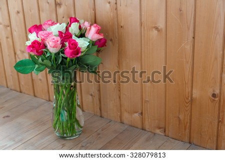 Vase with flowers standing near the window