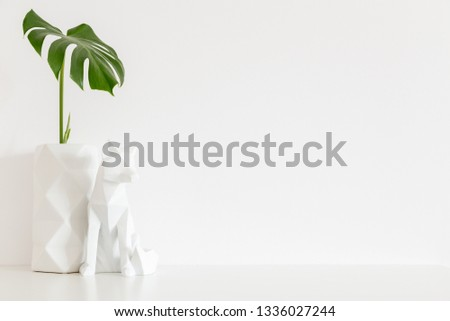 Vase with monstera leaf and origami decor on white wall with copy space.