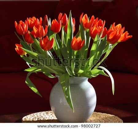 Vase with Orange Tulips in Modern Interior. Crackle-glazed vase, round place-mat of water hyacinth; background of burgundy-red sofa.