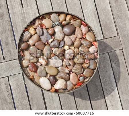 Vase with pebble stone decor on old gray wooden table