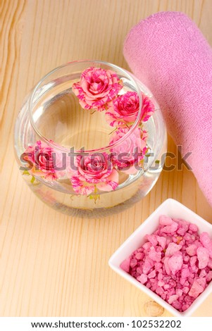 Vase with roses, spa setting on wooden background