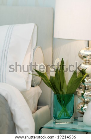 Vase with white tulips on the drawers in the bedroom