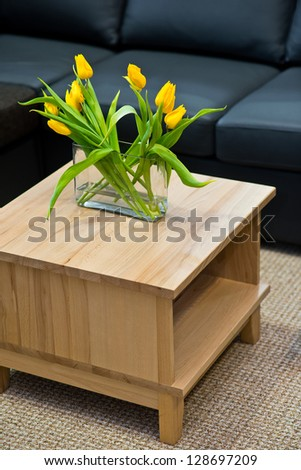 Vase with yellow spring tulips on modern wooden coffee table